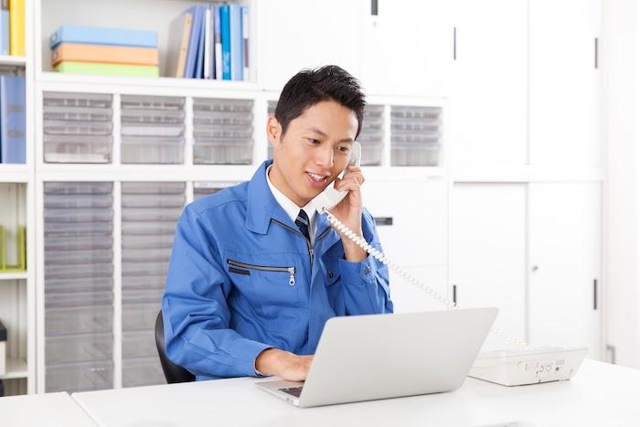 パソコンを見ながら電話をする男性